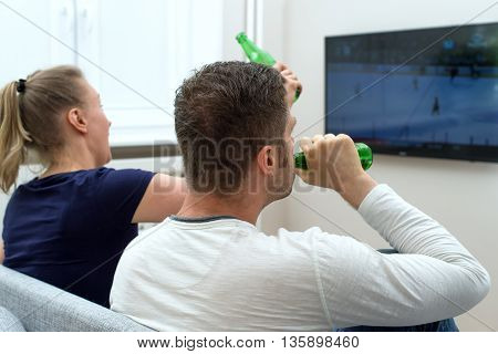 Excited Couple Watching Hockey Match On Tv.
