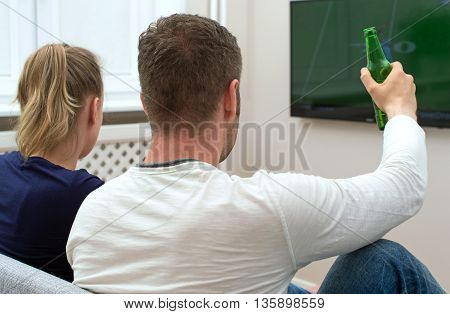 young couple watching American football on tv.