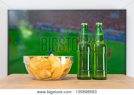 Beer and chips in front of TV with football match.