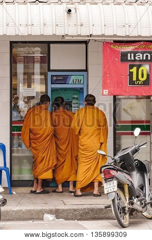 PHETCHABURI THAILAND - SEPTEMBER 14 2010. A group of buddhist monks withdraw some cash from an autoteller in the city.