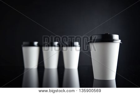 One focused white coffee take away paper cup ahead others unfocused, all closed with black caps presented on black and mirrored. Space for your text above