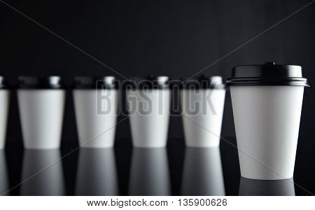 One focused white coffee take away paper cupin front of many unfocused in row line, all closed with black caps presented on black and mirrored. Retail mockup presentation