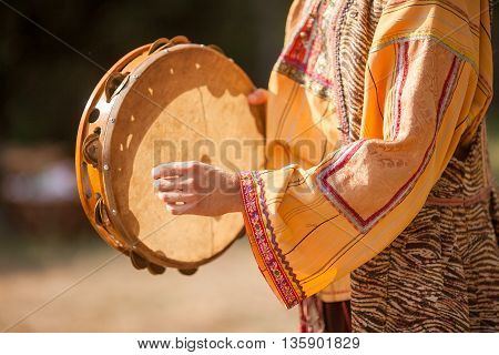 The woman in a national suit. Hand of the woman and tambourine. Playing a tambourine.