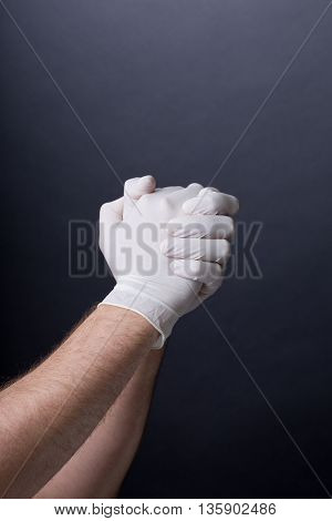 Male hands in golves. Clasped hands. Doctor or nurse wearing latex gloves. . Dark background