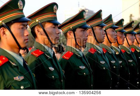 Beijing China - May 1 2005: A row of somber Chinese soldiers watch the evening flag-lowering ceremony in Tiananmen Square