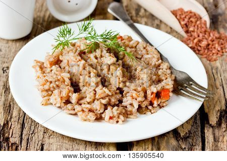 Delicious and healthy pilaf of medium-grain red matta (devzira) rice on old wooden table selective focus