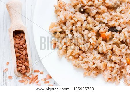 Vegetarian pilaf of red rice devzira with mushrooms and vegetables