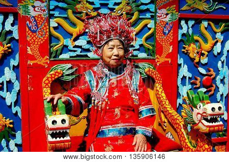 Beijiing China - May 5 2005: Woman wearing traditional Chinese ceremonial robe and ornamental headdress at the Dragon Wall in Jingshan Park