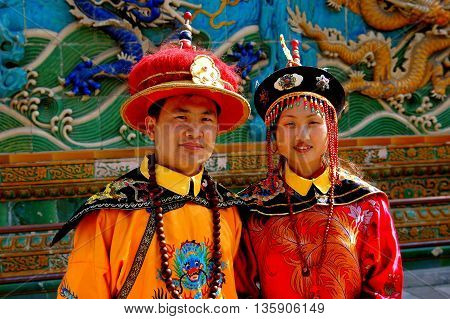Bejing China - May 5 2005: Young couple pose in rented traditional Chinese robes and hats in front of the Screen of Nine Dragons in Behei Park