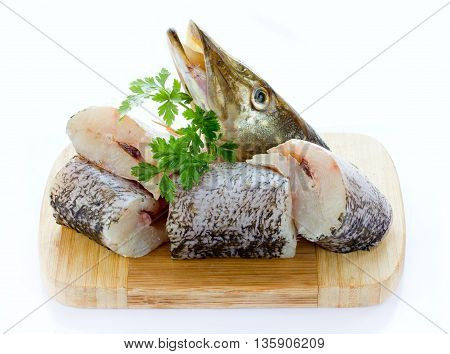 Pike fish pieces on a wooden board isolated on white background