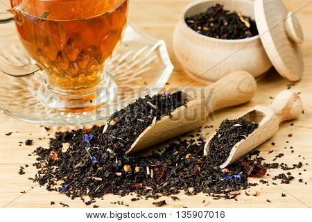 Tea composition with cup of tea and dried tea in wooden scoops on wooden background selective focus