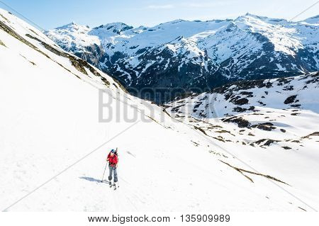 Female skier ascending a mountain slope. Ski touring in Malta valley, Austria.