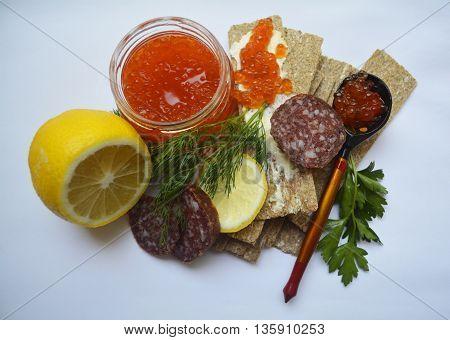 Breakfast of the aristocrat - red caviar, smoked sausage, bread, lemon, greens