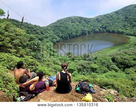 OMETEPE NICARAGUA - SEPTEMBER 25 2015: Group of tourists on the shore of lake in the crater of an extinct volcano Maderes on Ometepe Island in Nicaragua