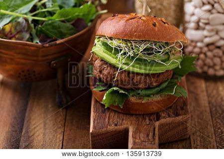 Grilled vegan bean burger with avocado, salad and cucumber