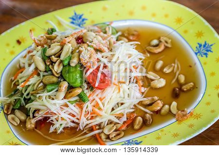 Thai style spicy green papaya salad (som tum Thai) in the yellow plate