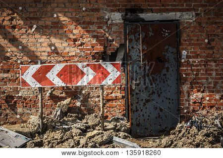 Flecked with shrapnel brick wall, door and road sign from parking of Donetsk airport after heavy and continuous shelling.