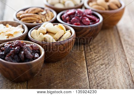 Variety of nuts and dried fruits in small wooden bowls healthy snacks