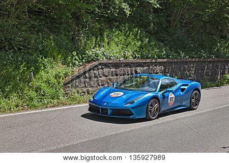 PASSO DELLA FUTA (FI) ITALY - MAY 21: driver and co-driver on a sports car Ferrari 488 Spider (2016) in rally