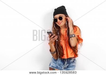 beautiful woman in sunglasses wearing in black hat and orange T-shirt listening music near white wall, holding a cell phone in hand, fashion concept