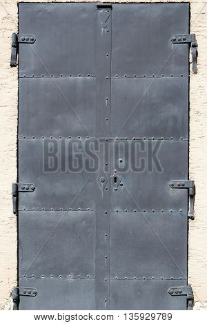 Hard old black medieval iron metal door with rivets and lock
