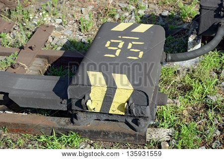 Roughly painted case of electric railroad switch actuator is in sunlight on Ukrainian railway.