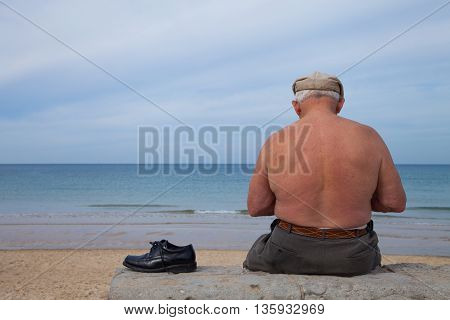 Old man sitting alone at the beach