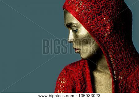 Young woman with golden painted face in red knitted jacket with hood on grey background closeup copy space