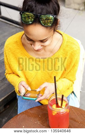Young Woman Sitting At Cafe Using Mobile Phone