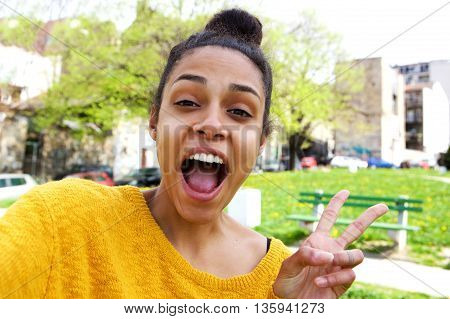 Excited Young Woman Taking Selfie With Peace Sign