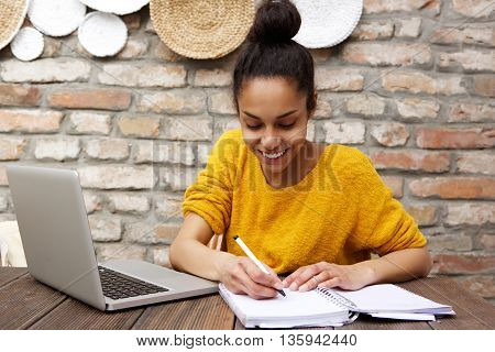 Young Black Woman Sitting At Cafe With Laptop And Notebook