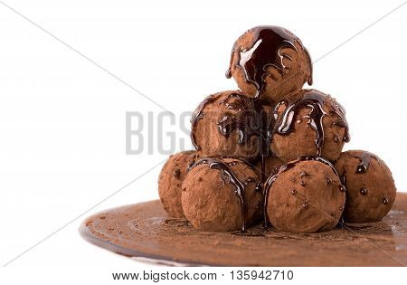 Chocolate truffles formed like a pyramid with melted chocolate