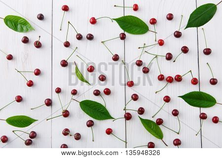 Sweet fresh cherries and leaves background. Scattered frutis on white rustic wood, top view.