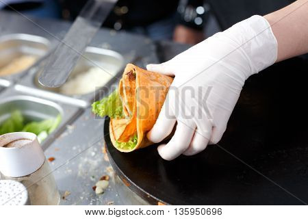 Making vegetable crepe, roll with tomatoes and lettuce. Salty crepe or pancake with fillings made by street vendor's hands at outdoors creperie. French cuisine, cooking for commercial kitchen. poster