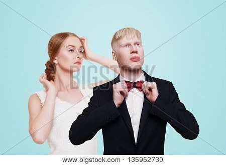 Modern beautiful good looking lady in white dress and gentleman in black suit with bow tie. Well-dressed couple, man and woman. Cool pale albino guy and redhead girl. Fashion models, mannequins