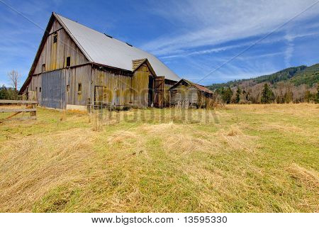 Large Old Rustic Grey Barn In The Field With Mountain