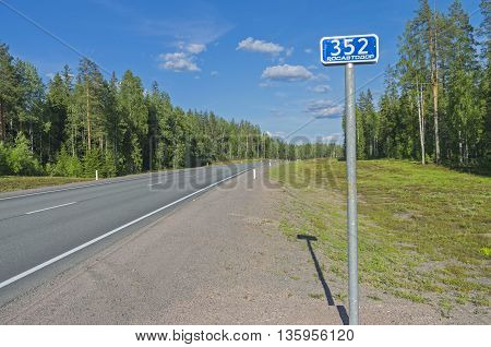 Milepost on the federal highway A121. Sunny day in June. South Karelia Russia.