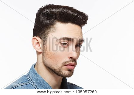 Closeup portrait of handsome man with black hair demonstrating his modern hairstyle over white background in studio. Hairdressing concept.