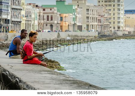 HAVANA - CUBA JUNE 20, 2016: Boy and older man fishing from the seawall of the Malecon with historic homes of the city behind them.