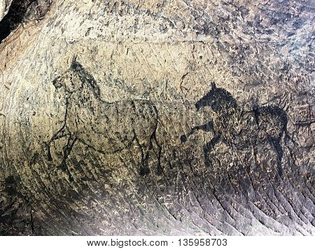 Abstract children art in sandstone cave. Black carbon paint of horses on sandstone wall copy of prehistoric picture.