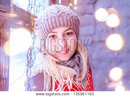 cute girl in knitted hat smiling happily. beautiful blonde girl is happy at Christmas on the background of Christmas lights. look at the camera winter holidays, christmas, party and happiness concept