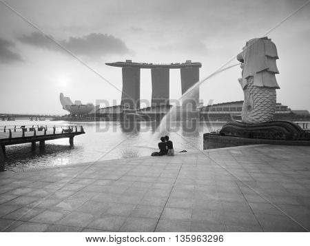 SINGAPORE - MARCH 10 2013: Couple sitting relax in the morning at Merlion Park Marina Bay. Merlion is a mythical creature with the head of a lion and the body of a fish is a symbol of Singapore.