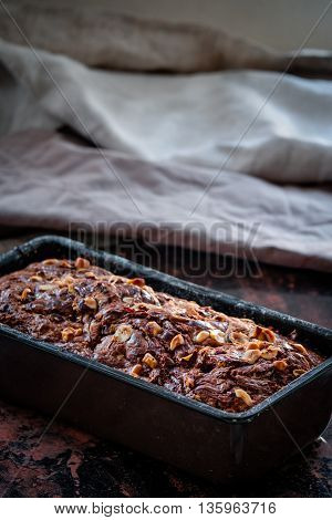Banana bread with nutella swirl and chopped hazelnuts in the baking pan. Dark food photography. Free text space.