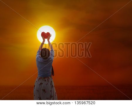 Women Gently Hold Red Heart To The Sun
