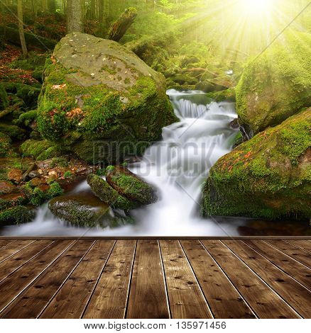 Waterfall on a mountain creek in the foreground a wooden planks.