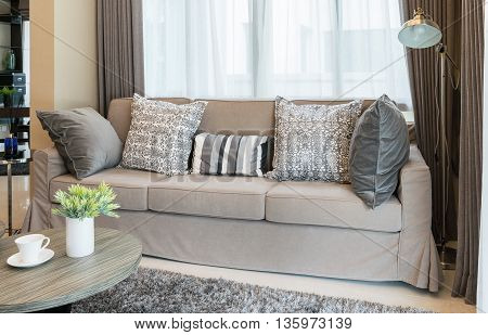 Sturdy Brown Tweed Sofa With Grey Patterned Pillows