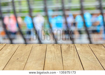 Empty wooden table or plank with blurry shot of people walking at bridge on background for product display.