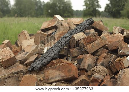 firebrand smouldering piece of wood on broken bricks