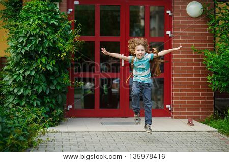 The little first grader rejoices to the beginning of summer vacation. He runs out from doors of school. As if flies. On a face of the school student expression of happiness.