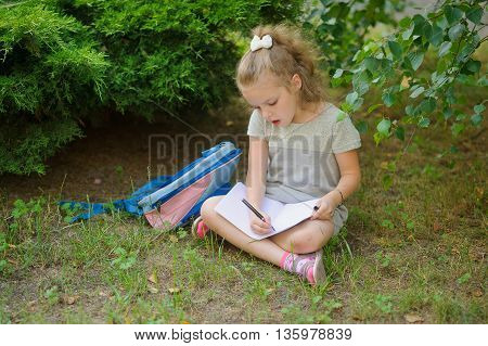 First grader sits having crossed legs under a tree and does homework. Girlie has a thoughtful look. Near the girl her satchel lies. Back to school.